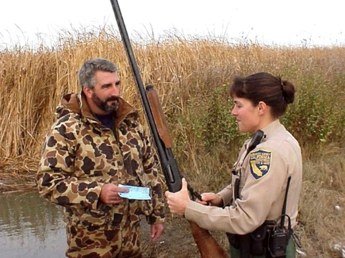 Game warden Nicole Kozicki checks a waterfowl hunter's hunting license
