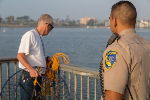 Wildlife officer and hoop netter on pier