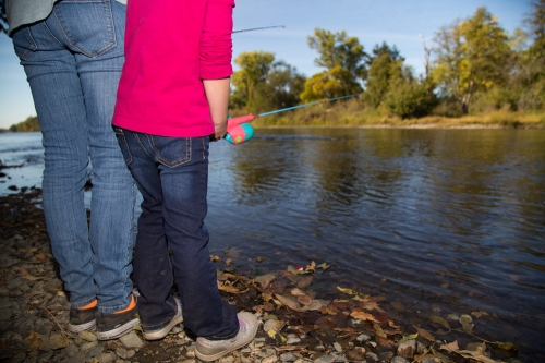 Little girl fishing with parent